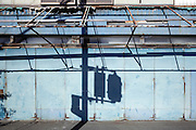 shadow of traffic lights on a closed up store front wall by an abandoned promenade