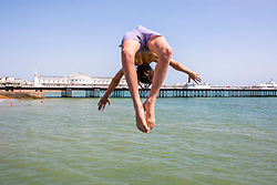 © Licensed to London News Pictures. 23/06/2020. Brighton, UK. Kids can be seen jumping of the pontoon in the sea in Brighton and Hove as hot and sunny weather is hitting the seaside resort. Photo credit: Hugo Michiels/LNP