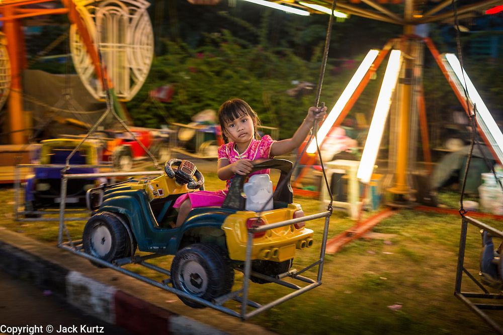 09 FEBRUARY 2014 - HAT YAI, SONGKHLA, THAILAND:  A child on a midway ride at the street fair during Lunar New Year in Hat Yai. Hat Yai was originally settled by Chinese immigrants and still has a large ethnic Chinese population. Chinese holidays, especially Lunar New Year (Tet) and the Vegetarian Festival are important citywide holidays.     PHOTO BY JACK KURTZ