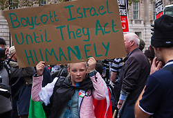 Downing Street, London, November 15th 2014. Dozens of Palestinians and their supporters faced a small group of Israeli counter protesters as they demonstrated outside the gates of Downing Street against Israel. Police had to intervene as several from both sides took exception to what was being said, with the half-dozen-strong Israeli group eventually moving off. Pictured: A girl calls for a boycott of Israel.