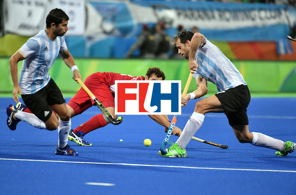 Belgium's Tanguy Cosyns (C) falls down as he vies with Argentina's Juan Lopez (L) and Argentina's Facundo Callioni during the men's Gold medal field hockey Belgium vs Argentina match of the Rio 2016 Olympics Games at the Olympic Hockey Centre in Rio de Janeiro on August 18, 2016. / AFP / Pascal GUYOT        (Photo credit should read PASCAL GUYOT/AFP/Getty Images)