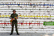 Man dressed as soldier with coloured weapon in front of United Colors of Benetton poster in 1980s in Italy