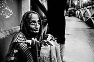 En ældre kvinde tigger. Dhaka der er hovedstaden i Bangladesh har store fattigdoms og overbefolkningsproblemer, da byen vokser med et kolosalt tempo pga. urbaniseringen som er følger efter klimaforandringer og naturkatastrofer som er med til at gøre livet sværre i storbyen, da mange flytter fra landdistrikterne. Der er mange tiggere og hjemløse i Dhaka.
