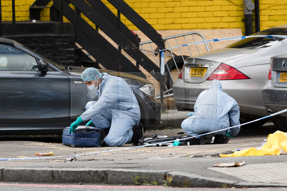 © Licensed to London News Pictures. 08/08/2017. LONDON, UK.  Forensic officers at the crime scene cordon on the corner of Old Kent Road and Ilderton Road, next to the Afrikiko Bar Restaurant and Club. Police were called at around 2am and found a 19 year old man with stab injuries, who was pronounced dead about an hour later. Five people have now been arrested in connection with stabbing and are being held at a south London police station.  Photo credit: Vickie Flores/LNP