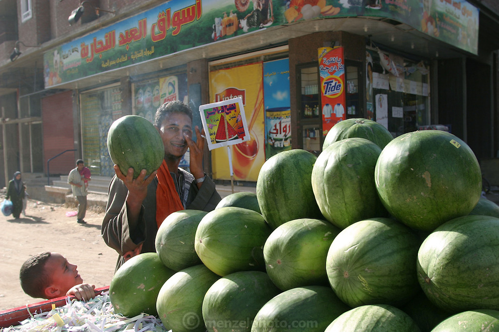 A watermelon vendor outside a small supermarket in Cairo, Egypt. (Supporting image from the project Hungry Planet: What the World Eats.)