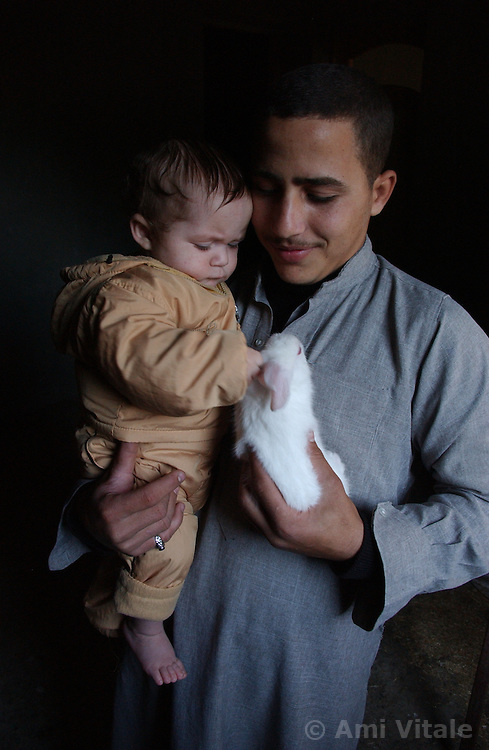 Fayoume, Egypt: Wael,16, who lives in Hamidia village in Fayoume, Egypt shows a neighbor, Ahmad, 6 months, one of his rabbits that is part of a telefood program funded byt FAO December 7, 2005.   The project has given him enough money to pay for school and buy goats for his family. .(Photo Ami Vitale)