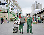 Two porters at the Port of Makassar, Sulawesi. As modern system is yet to be employed, porters still play a very important role carrying passengers' goods onto the ships.<br /> <br /> Indonesia&rsquo;s Pelni is the last great true passenger liners company in the world. It is the only company of its size that still serves scheduled vessels transporting people across various destination. In a far-flung archipelago nation, where many of the islands have no airport and most of its area made up of water, it is one important mean of transportation&mdash;and simply one of the best way to travel. One of Pelni's furthest regular route starts from Surabaya in East Java and ends in Papuan city of Merauke, basically the eastern end of Indonesia. The round trip voyage takes one month, passing more than two dozen ports and covering a distance of more than 8,000 kilometers.
