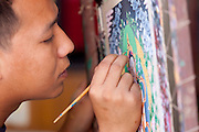 Artists creating traditional Tibetan Buddhist thangkas. The silk is decorated with Buddhist deity's, mandala symbols and other icons associated with Tibetan Buddhism.