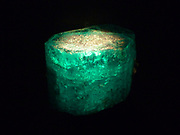 Glowing minerals.  A number of different minerals appear to glow in the dark when they are energized by ultraviolet light, invisible to our eyes.  They release this energy as light in a part of the spectrum we can see.  This phenomenon is known as fluorescence.