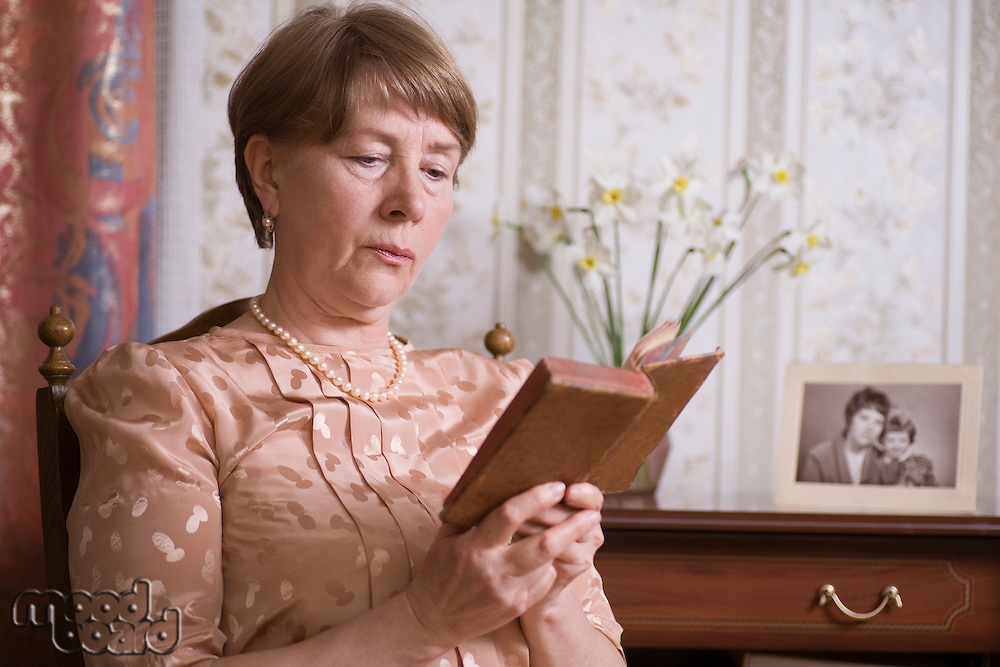 Elderly woman sits reading book in Russian apartment