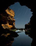 The Grotto is located on the Western End of the Great Ocean Road and offers a stunning natural archway out to the Southern Ocean. <br /> On a still clear night i visited the area, looking to capture a star trail. The full moon was giving an amazing light on the cliff edge and the long exposure created the star trail, with a nice bonus of the reflection in the still clear waters of the rock pool.