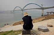 Man watches construction of a railway bridge in Yichang, China