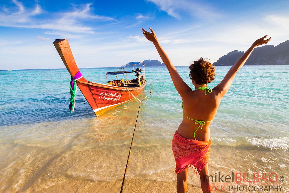 Young woman relaxing.  Long beach. Phi Phi Don island. Krabi province, Andaman Sea, Thailand.