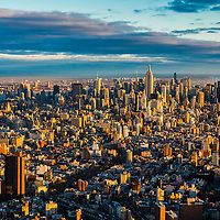 Aerial photograph of midtown Manhattan at sunrise with golden light, New York City.