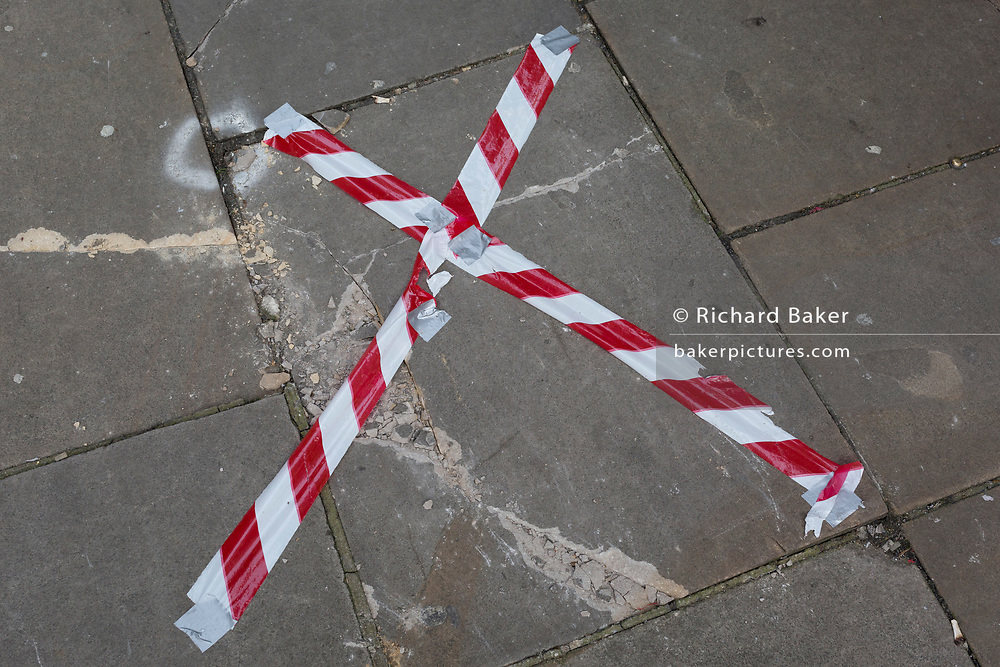 Hazard tape is stretched across a broken paving slab on a Clerkenwell Street in the borough of Islington, on 20th November 2019, in London, England.