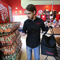 Blake Richardson, a delivery driver for Tupelo 2 Go, checks his phone as he leaves Neon Pig with a customers lunch order. Next month, Tupelo 2 Go will celebrate its two-year anniversary. They have expanded their service to include the Mooreville and Saltillo areas and increased their delivery drivers from 4 to 30. Feburary will also be Richardson's two anniversary with the delivery business.