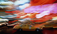 The magic lights of Times Square woven around a moving taxi, New York City, USA