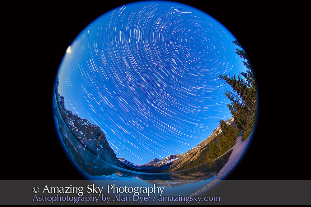 A composite of about 90 images, taken with the Canon 5D MkII and 8mm Sigma fish-eye lens, at Bow Lake in Banff, July 6, 2012, showing star trails across the sky looking west. The Moon is just coming up at left. A meteor appears above Bow Peak. Each image was 50 seconds, taken at 1s intervals at ISO 1250 and at f/4. Stacked in Photoshop using Chris Schur's Photoshop Action.