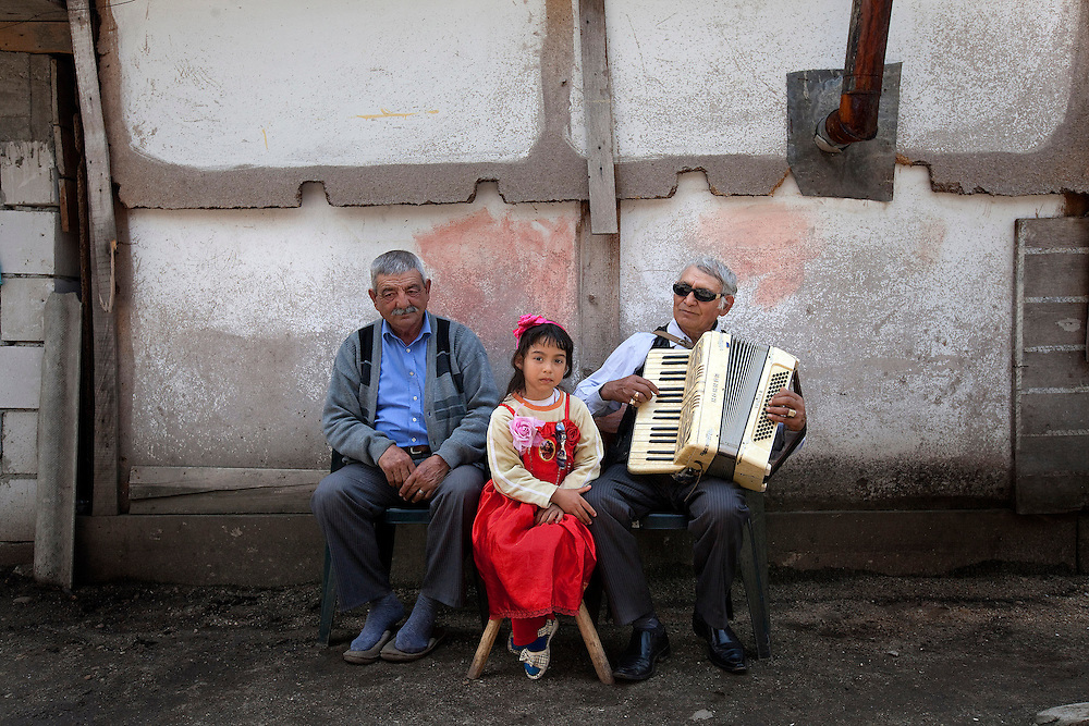 Jasmin Iancu, 6, sits between Marin Nicolae, and her grandfather, Ion Iancu in Buzescu, a small town in Romania.
