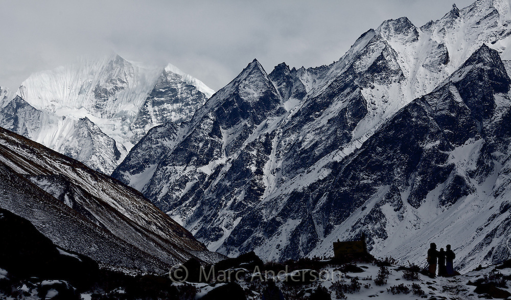 Trekkers standing beneath snowcapped mountains along the Langtang Valley, Nepal