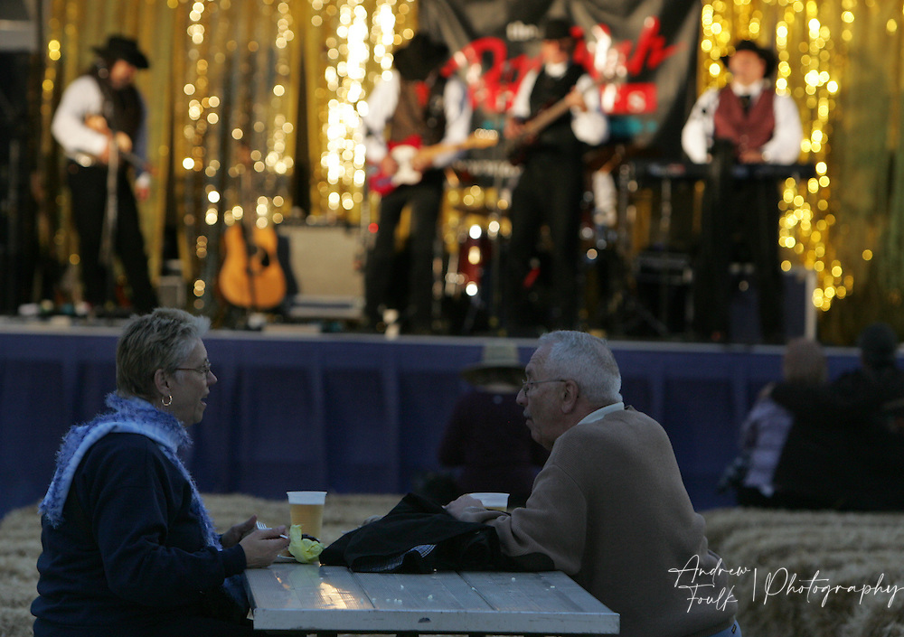 /Andrew Foulk/For The Californian/.Lynn and Don Durbin, of Perris, sit and enjoy a dinner of fair cuisine as they listen to a country band perform at the Southern California Fair in Perris.