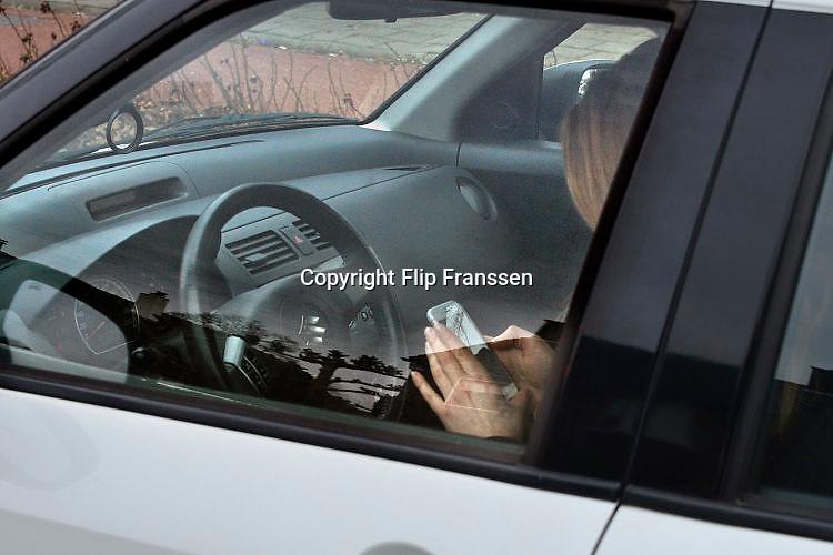 Nederland, Nijmegen, 25-2-2017Een jonge vrouw zit in de auto achter het stuur terwijl ze met haar telefoon, mobieltje, smartphone bezig is. Ze zit te appen ,Foto: Flip Franssen