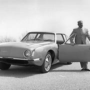 Raymond Loewy poses with a Studebaker Avanti.