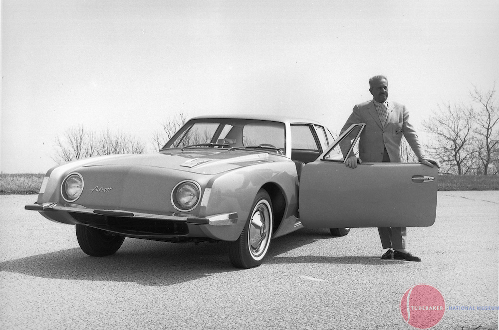 Raymond Loewy poses with a Studebaker Avanti.