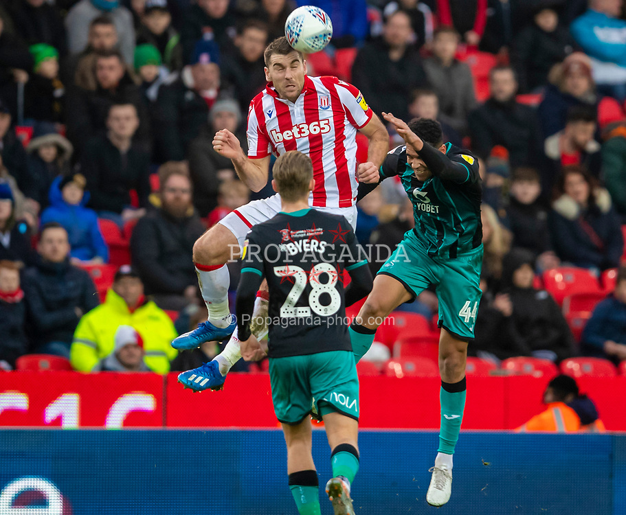 STOKE-ON-TRENT, ENGLAND - Saturday, January 25, 2020: Stoke City's Sam Vokes challenges for a header with Swansea City's Ben Cabango (R) during the Football League Championship match between Stoke City FC and Swansea City FC at the Britannia Stadium. (Pic by David Rawcliffe/Propaganda)