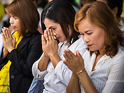 26 DECEMBER 2014 - MAE KHAO, PHUKET, THAILAND: Thai women pray during the memorial service at the Tsunami Memorial Wall in Mae Khao, Phuket. The wall is located at the site that was used as the main morgue for people killed in the tsunami and hosts an annual memorial service. Nearly 5400 people died on Thailand's Andaman during the 2004 Indian Ocean Tsunami that was spawned by an undersea earthquake off the Indonesian coast on Dec 26, 2004. In Thailand, many of the dead were tourists from Europe. More than 250,000 people were killed throughout the region, from Thailand to Kenya. There are memorial services across the Thai Andaman coast this weekend.    PHOTO BY JACK KURTZ