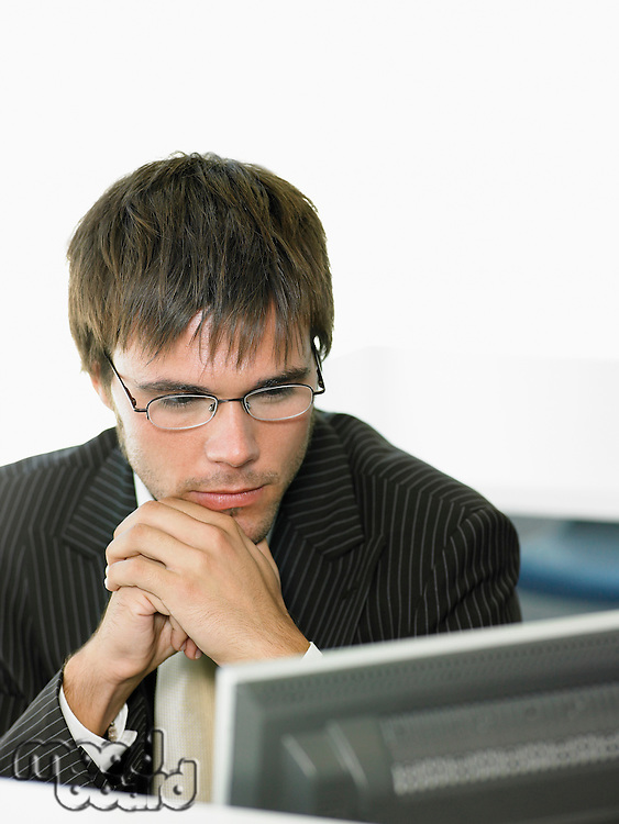 Serious Businessman looking at computer screen in office