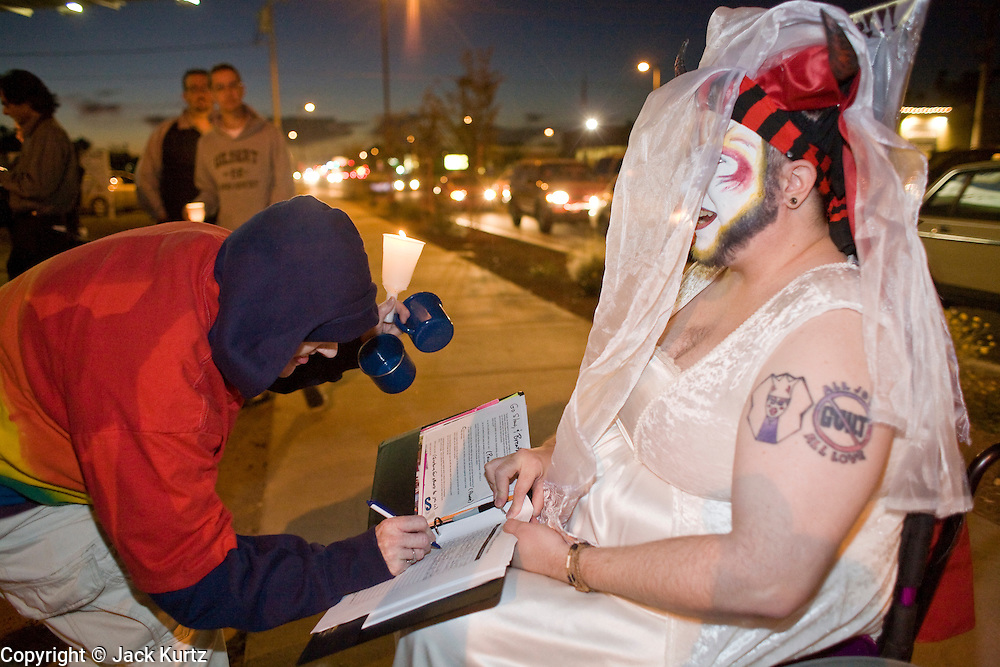 November 10, 2008 -- PHOENIX, AZ:  A person signs a petition with Sister Mischif of the Arizona Sisters of Perpetual Indulgence during a gay rights vigil in Phoenix Monday night. About 250 people attended a candle light vigil in support of gay rights and gay marriage in Phoenix, AZ, Monday night. The rally, like similar ones in Los Angeles and Salt Lake City, were in response to anti-gay marriage and anti-gay rights initiatives that were passed by the voters in Arizona, California and Florida. The anti-gay initiatives in Arizona and California were funded by conservative churches, including the Church of Latter Day Saints (Mormons). Photo by Jack Kurtz / ZUMA Press