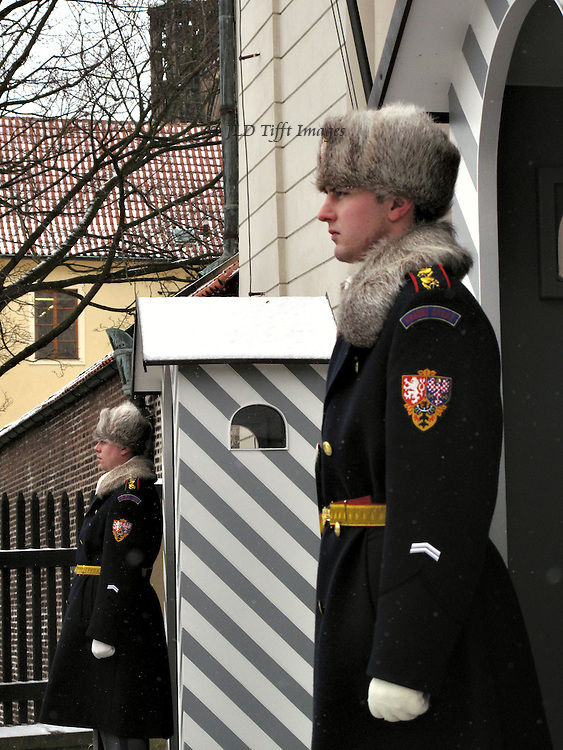 Two young men in  guard uniform with fur hats and rosy cheeks stand solemnly at attention at an entrance to Hradcany Castle, Prague.  A guard hut is between them.  They are seen in profile, three quarter view.