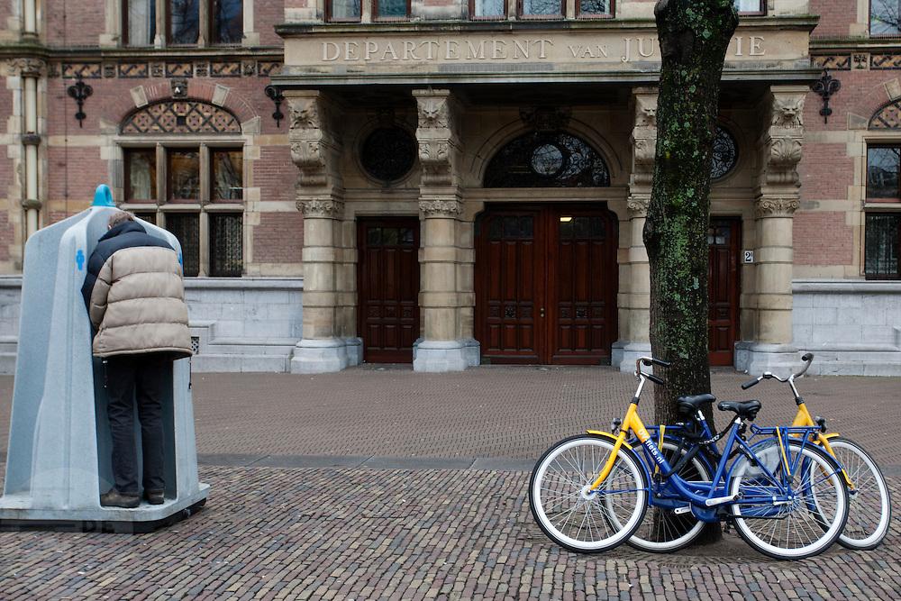 Een man staat te plassen in een plashokje op het Plein in Den Haag.<br /> <br /> A man is urinating at a public toilet at the Plein in The Hague.