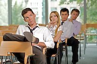 Business executives sitting in row at office
