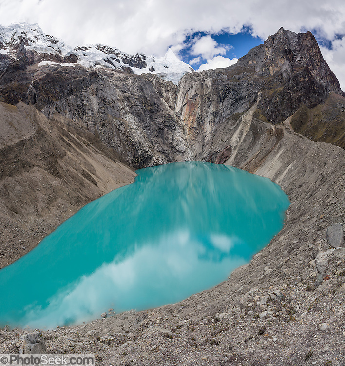 The turquoise waters of Jancarurish Lake are colored by glacial flour from Nevado Alpamayo (19,511 ft or 5947 m), in Alpamayo Valley, Cordillera Blanca, Andes Mountains, Peru, South America. Day 7 of 10 days trekking around Alpamayo, in Huascaran National Park (UNESCO World Heritage Site). This panorama was stitched from 7 overlapping photos.