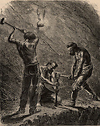 Cornish miners boring a hole to take a charge of explosive.  One miner holds the metal borer upright and the two strikers hit it with sledge hammers until the hole has been made. Cornwall, England.   From 'Underground Life; or, Mines and Miners' by Louis Simonin (London, 1869). Wood engraving.