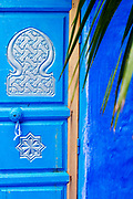 CHEFCHAOUEN, MOROCCO - 29th MARCH 2014 - Close up of blue doorway architecture with decorative palm tree, Chefchaouen Medina - the blue city, Rif Mountains, Northern Morocco.
