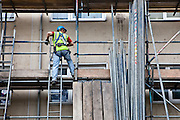 A workman erects scaffolding so that external cladding can begin on a maisonette block. Northwards housing have dramatically improved the energy rating to thousands of homes they manage for Manchester city council.