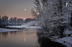 The moon sets over the Chilkat River during sunrise in the Alaska Chilkat Bald Eagle Preserve near Haines, Alaska. During late fall, bald eagles congregate along the Chilkat River to feed on salmon. This gathering of bald eagles in the Alaska Chilkat Bald Eagle Preserve is believed to be one of the largest gatherings of bald eagles in the world. In 1982, the 48,000 acre area was designated as the Alaska Chilkat Bald Eagle Preserve.