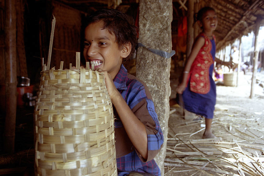 India. Tamil Nadu. Chennai (Madras). 2002. A thirteen- year-old child labourer uses his teeth to finish of making a bamboo basket while another child worker runs past. Vasudhevarao, is part of small community of about ten families who come from different parts of Andhra Pradesh to Tamil Nadu to do this work. The community's occupation in A.P. is also making baskets but there is not enough demand all year round so they move for several months at a time to find work. All children in the community once they're ten-years-old learn how to make baskets to boost production. The parents explain how the main reason for not sending the children to school is because of administrative complications and the language problem; they don't speak the local Tamil language. The parents also explain how they need the children to work along side them to increase their production.