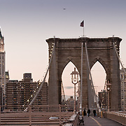 The Woolworth Building and the Brooklyn Bridge in the setting sun.