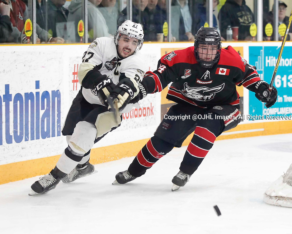 TRENTON, - Apr 17, 2016 -  Ontario Junior Hockey League game action between the Trenton Golden Hawks and the Georgetown Raiders. Game 3 of the Buckland Cup Championship Series, Danny Hanlon #27 of the Trenton Golden Hawks and Zachary Dybowski #14 of the Georgetown Raiders battle for the puck at the Duncan Memorial Gardens, ON. (Photo by Amy Deroche / OJHL Images)
