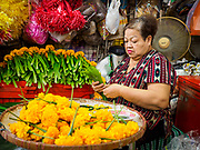 10 JULY 2018 - NAKHON PATHOM, THAILAND:  A woman in the Nakhon Pathom market makes floral garlands. Nakhon Pathom is about 35 miles west of Bangkok. It is one of the oldest cities in Thailand, archeological evidence suggests there was a settlement on the site of present Nakhon Pathom in the 6th century CE, centuries before the Siamese empires existed. The city is widely considered the first Buddhist community in Thailand and the nearly 400 foot tall Phra Pathom Chedi is considered the first Buddhist temple in Thailand.    PHOTO BY JACK KURTZ