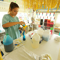 Dawson Crawford, an employee at Rockin' Robin Shaved Ice & Refreshments, uses a slow moment in her day to mix up flavors that have gotten low throughout the day.