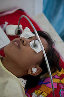 """June 2011 Cataract Operation in P. Sidempuan and Medan, Indonesia . Photographs by Michael Amendolia . Story researched by Susilawaty.The Story of Maslia and Nurasni LubisMaslia Lubis 15 and her sister Nurasni 19 are from jalan Sibolga, Desa (village) Sipenggeng in Batang Toru, 26kms from Padang sidempuan in North Sumatra,They were bilateral blind, means blind in both eyes. Cause of their blindness is cataract, a disease curable by an eight-minute operation. Yet Maslia had been blind since she was 3, and Nurasni since 5.Maslia's poor vision was noticed by her parents when she a toddler, she could not find toys she was playing with after they were dropped.Even with her impaired vision, Maslia is determined to continue studying and is a smart student. She is in secondary 3 (SMP 3), and although she can't see or write, she can hear and speak. She managed to be ranked 3rd in her class on her academic results.But it is difficult for her to enjoy school activities. She can't participate in sports. And she can't go to school on her own. She needs school mates' help.Maslia was always hopeful to regain her sight and often asked her parents to take her to clinics. But all the clinics they'd been could not cure her.Her parents (Sari Alam and Mara Aman Lubis), who rely on farming income from a quarter hectare land to feed a family of 6, could not afford to keep on spending on experimental treatment.Whilst Maslia is a confident and hopeful young girl, Nurasni has become the opposite.Constant teasing by friends calling her """"blind girl"""" and inability to keep up with school her led to a low self-esteemed. Nurasni eventually dropped out of school after Primary 5 (SD 5). She had also somehow, accepting her fate. She never asked her parents to take her to clinics.Dr. Sanduk Ruit of Tilganga Institute of Ophthalmology - Nepal, operated both girls on The 16th June 2011 at the Military Hospital in Padang Sidempuan.Their vision was restored the very next day.Visiting the market and buying"""