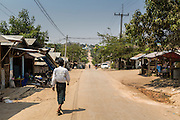 02 MARCH 2014 - MYAWADDY, KAYIN, MYANMAR (BURMA):  A man walks down a road in a residential section of Myawaddy, Myanmar. Myawaddy is separated from the Thai border town of Mae Sot by the Moei River. Myawaddy is the most important trading point between Myanmar and Thailand.     PHOTO BY JACK KURTZ