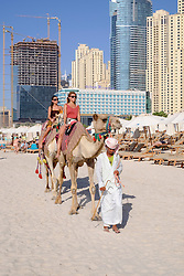 Tourists riding camel on beach at JBR Jumeirah Beach Residences in Marina district of Dubai United Arab Emirates