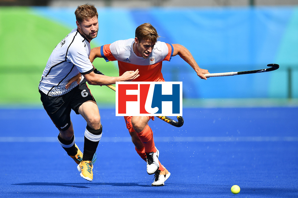 Germany's Martin Haner (L) and Netherlands' Jeroen Hertzberger vie during the mens's field hockey Germany vs Netherlands match of the Rio 2016 Olympics Games at the Olympic Hockey Centre in Rio de Janeiro on August, 12 2016. / AFP / MANAN VATSYAYANA        (Photo credit should read MANAN VATSYAYANA/AFP/Getty Images)