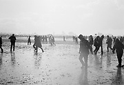 View of hooded people walking in muddy field in the rain. Glastonbury 1997